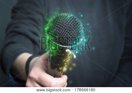 Microphone in hand with sparkle. Close up.