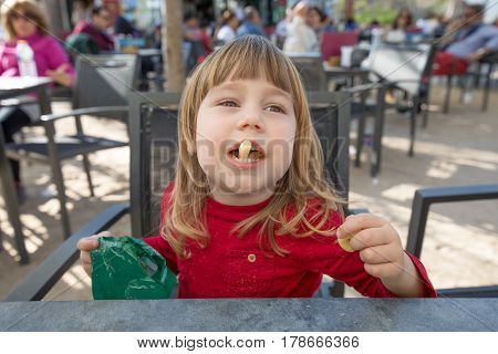 Child Sitting In Exterior Bar Eating Cheese Puff