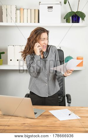 Furious Businesswoman Screaming On Mobile With Document In Hand