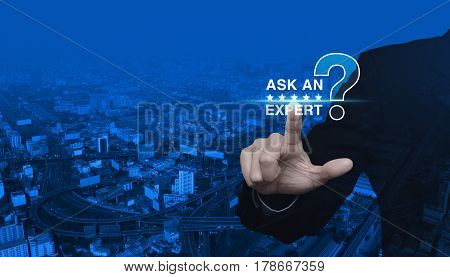Businessman pressing ask an expert with star and question mark sign icon over modern city tower street and expressway