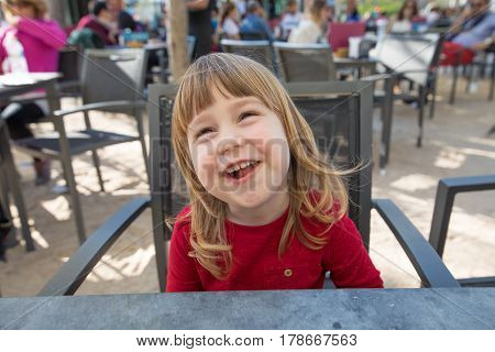 Portrait Of Laughing Child Sitting In Exterior Bar