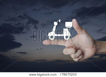Motor bike icon on finger over sunset sky Business delivery service concept