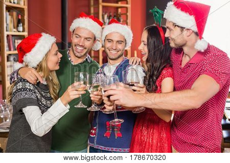 Friends with Christmas hats in a bar toasting