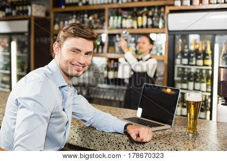 Handsome man smiling at camera with laptop while an attractive barmaid cleaning glass