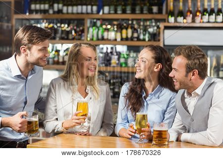 Attractive friends talking at a bar while holding glasses of beer
