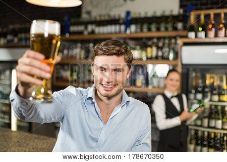 Man toasting a beer with barmaid behind him