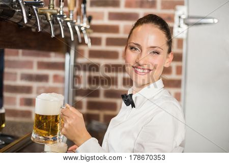 Attractive barmaid holding beers while smiling at camera in a bar