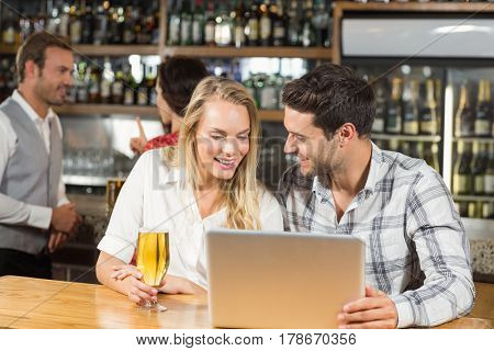 Attractive couple looking at laptop in a bar