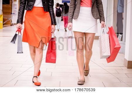 Women walking with bags while shopping in mall