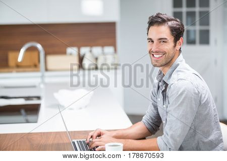 Portrait of smiling young man working on laptop at home