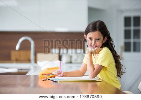 Portrait of smiling girl with hand on chin while sitting at desk in home
