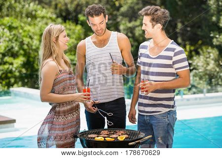 Happy friends talking to each other while preparing barbecue near pool