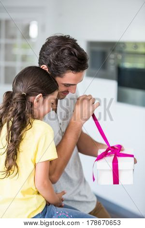Father opening gift given by daughter at home