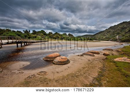 Wooden Footbridge Across Tidal River On Stormy Weather. Wilsons Promontory, Victoria, Australia.
