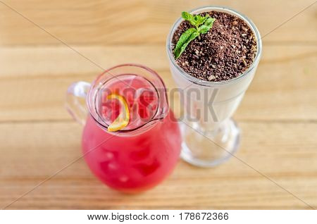 Red juice in a jug with lemon and a white cocktail in a glass with chocolate and mint on a wooden table
