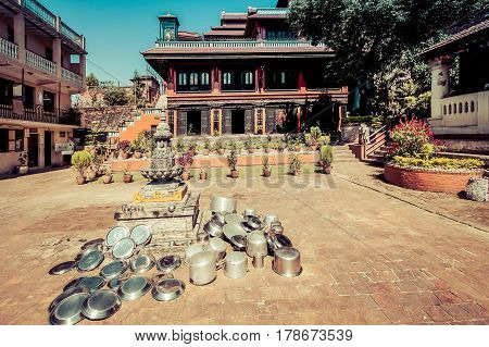Bhaktapur, Nepal - October 8, 2011: Metal Dishes Left To Dry Out In The Sun In Front Of A Buddhist M
