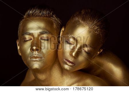 Male and female face around. The woman's head lies on the shoulder of a man. All painted in gold paint, the feeling of a single whole organism.