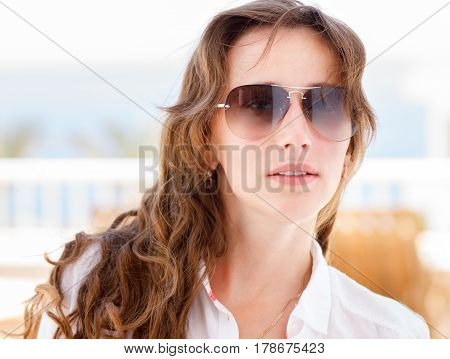 Portrait of young stylish woman in sunglasses with long curly hair