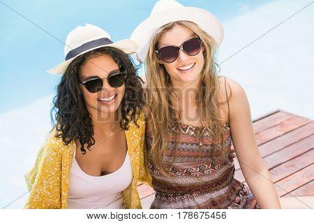 Young women wearing sunglasses having fun near pool on a sunny day