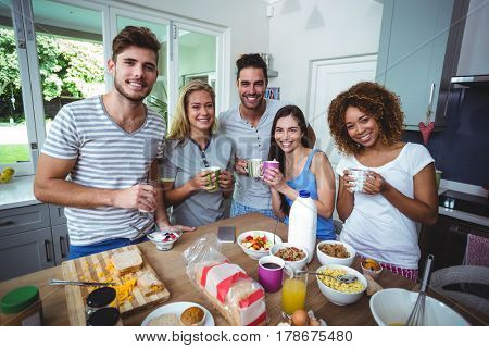 Portrait of cheerful friends holding drinks while standing at table