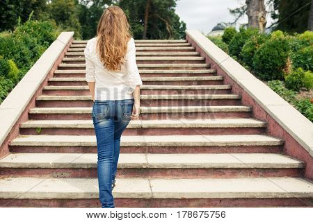 Rear view of young woman going up the stairs in the park