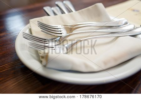 Close up image of forks and knives served on the table in restaurant. Cutlery background