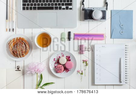 Feminine flat lay workspace with laptop cup of tea macarons photo camera and flowers on white wooden table. Top view mock up.