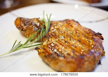 Close up image of beef steak on white plate with a twig of rosemary. Restaurant or steak-house menu background