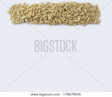 Pine nuts at border of image with copy space for text. Kernels nuts on a white background. Top view. Vegetarian or healthy eating. Background of pine nuts