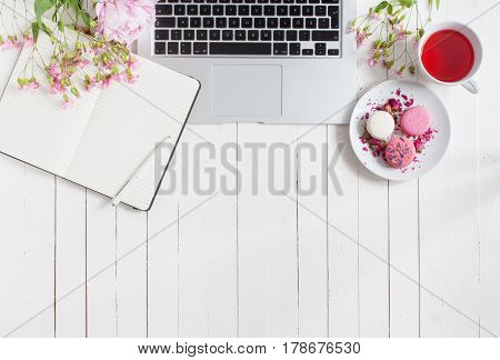 Feminine flat lay workspace with laptop notebook cup of tea macarons and flowers on white wooden table. Top view mock up.