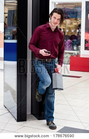 Man holding a shopping bags and using a mobile phone in mall