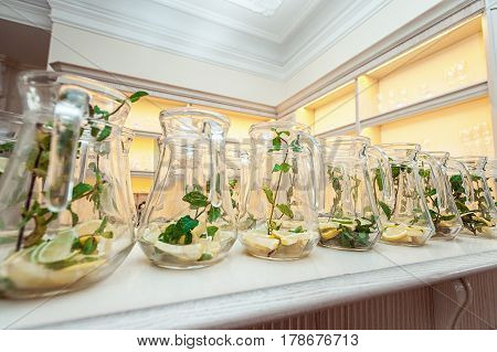 Rows of carafe mojito-style detox water in glass jar with lime, lemon and mint. Clean eating, diet.