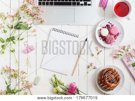 Feminine flat lay workspace with paintbrush notebook laptop cup of tea macarons and flowers on white wooden table. Top view mock up.