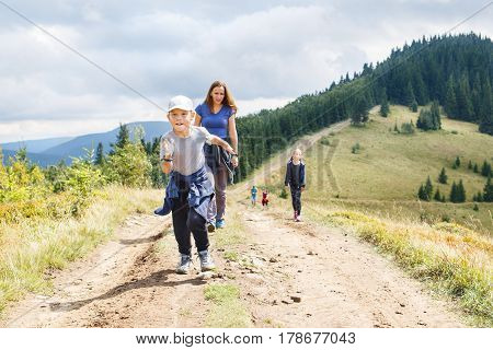 Happy small boy running towards the top of the hill with his family