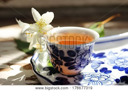 Tea tray and jasmine flowers. Cup of tea and jasmine flowers. Tea still life. Soft focus.