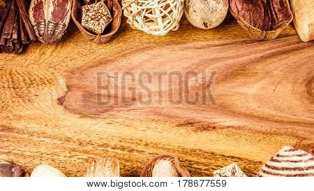 Aromatherapy potpourri mix of dried aromatic tropical seed and shell on wooden surface with empty space for text. Above and Bottom.