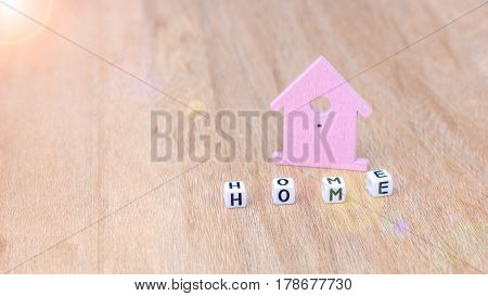 HOME word of cube letters in front of lilac coloured house symbol on wooden surface. Sun flares on left top corner.