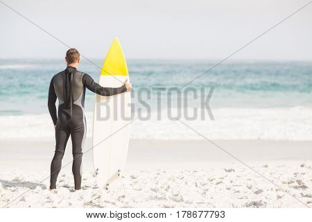 Rear view of man with surfboard standing on the beach on a sunny day
