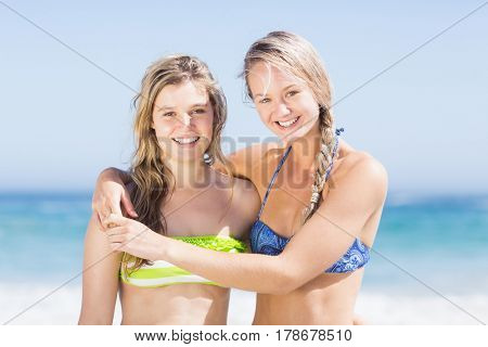 Portrait of two happy women in bikini standing on the beach on a sunny day