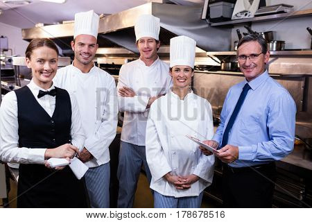 Portrait of happy restaurant team standing together in commercial kitchen