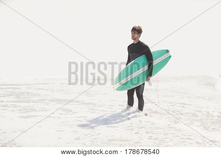 Man holding surfboard on the beach on a sunny day