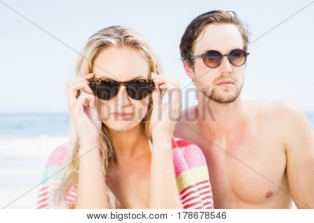 Young couple wearing sunglasses at beach on a sunny day