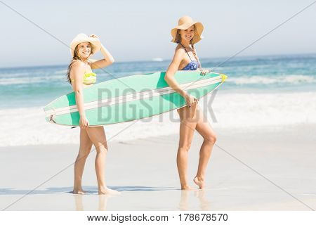 Two women carrying a surf board on the beach on a sunny day