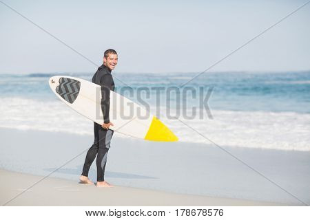 Surfer with a surfboard walking on the beach on a sunny day