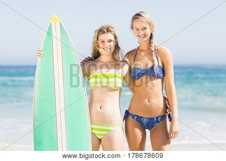 Portrait of two women in bikini standing with a surfboard on the beach on a sunny day