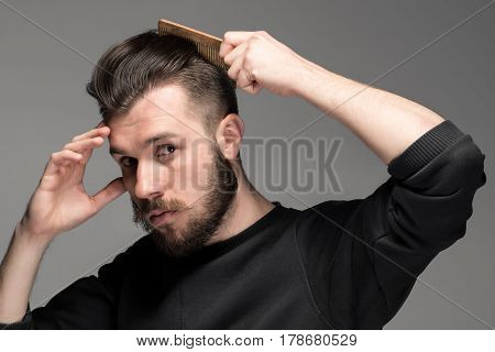 Portrait of stylish and handsome young man combing his hair
