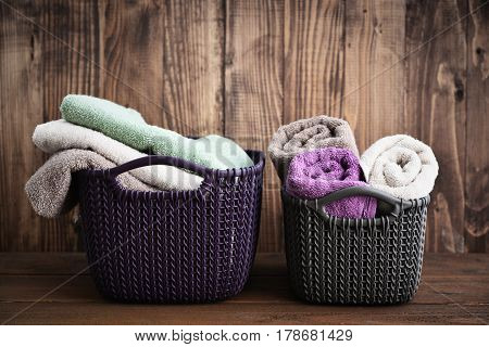 Bath towels of different colors in wicker baskets on wooden background