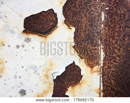 Corroded white metal background. Rusted white painted metal wall. Rusty metal background with streaks of rust. Rust stains. rust on old wall background