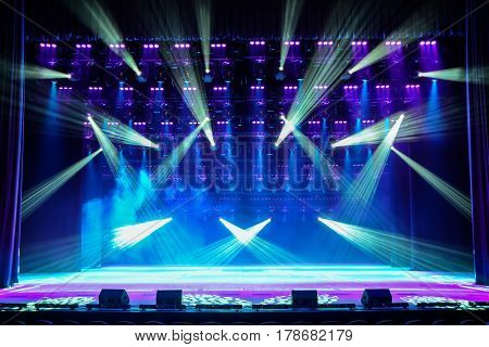 Illuminated empty show stage with blue light and stage fog