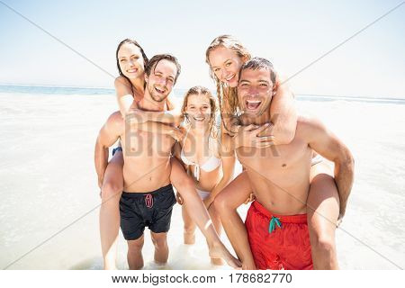 Men giving a piggy back to women on the beach on a sunny day